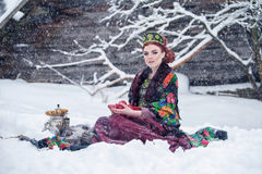 Portrait of a gorgeous young woman in russian style dress on a strong frost in a winter snowy day with apples and samovar. Royalty Free Stock Photography