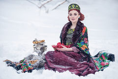 Portrait of a gorgeous young woman in russian style dress on a strong frost in a winter snowy day with apples and samovar. Stock Photo