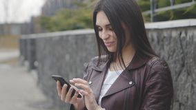 Portrait of gorgeous young woman using smartphone outdoor on the street. Girl is happy and smiling. Portrait of cute brunette woman using smartphone outdoor on stock video