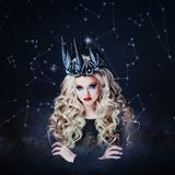 Portrait of a Gothic Princess. Beautiful young blonde woman in metal crown and black cloak. Against the starry sky stock photography