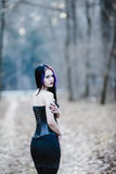 Portrait of the gothic woman in the dark forest. Portrait of the gothic woman in the dark winter forest royalty free stock photos