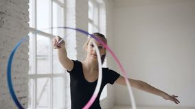 Portrait of graceful gymnastics spinning the colored ribbon in front of camera in the white studio on the window. Background and looking at the camera, slow stock footage