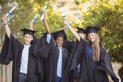 Portrait of graduate school kids standing with degree scroll in campus Stock Image