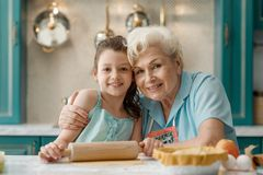 Portrait of granddaughter and grandma. Cooking at the kitchen table. Relatives hugging each other and giving happy smiles stock photo