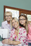 Portrait of granddaughter, grandmother and mother with sewing machine Stock Photos