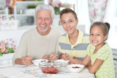 Grandfather and grandchildren eating fresh strawberries at kitch. Portrait of grandfather and grandchildren eating fresh strawberries at kitchen royalty free stock photography