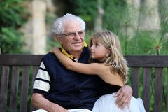Portrait of Grandfather and granddaugher. Grandfather and granddaughter sitting together an a bench in a park Royalty Free Stock Photo