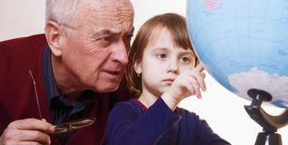 Portrait of grandfather and granddaughter looking at globe and planning travel