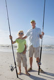 Portrait of grandfather and grandson with fishing rods on sunny beach Stock Photography