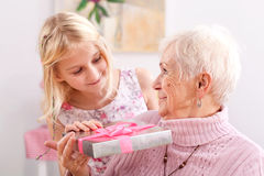 Portrait of grandma and granddaughter. With birthday gift Stock Image