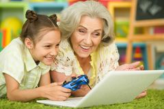 Portrait of grandmother and daughter playing computer game royalty free stock image