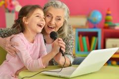 Portrait of grandmother and daughter singing karaoke stock photo