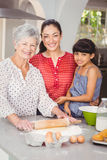 Portrait of grandmother with family making bread Stock Image