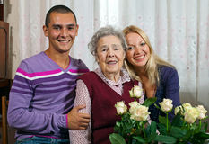 Portrait of grandmother and grandchildren. Visiting her on her birthday at her home. Grandmother holding bunch of roses Royalty Free Stock Image