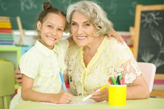 Portrait of grandmother and granddaughter drawing together royalty free stock photos