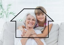 Portrait of grandmother and granddaughter overlaid with house shape in living room Royalty Free Stock Photos