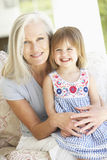 Portrait Of Grandmother And Granddaughter Sitting In Chair Royalty Free Stock Images