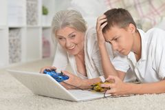 Portrait of grandmother and grandson playing computer game with Royalty Free Stock Photography