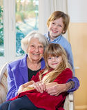 Portrait of a grandmother with her grandchildren. Portrait of an elderly grandmother and her grandchildren sitting in an armchair with the little girl on her royalty free stock photos