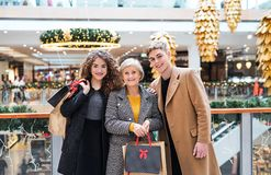 A portrait of grandmother and teenage grandchildren in shopping center at Christmas. Royalty Free Stock Photo