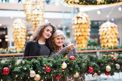 A portrait of grandmother and teenage granddaughter in shopping center at Christmas. Royalty Free Stock Photography