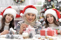 Grandmother with twin granddaughters preparing for Christmas royalty free stock photography