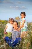 Portrait of   grandmother and two granddaughters. Beautiful grandmother with two granddaughters walking in  summer field stock photos