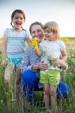Portrait of   grandmother and two granddaughters. Beautiful grandmother with two granddaughters walking in  summer field stock image