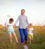 Grandmother with two granddaughters walking in  summer field . Portrait of   grandmother and two granddaughters of 4 and 6 years old royalty free stock image