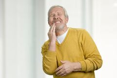 Portrait of grandpa with tooth disease. Old man suffering from tooth pain. Bright blurred background Stock Image