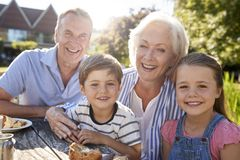 Portrait Of Grandparents With Grandchildren Enjoying Outdoor Summer Snack At Cafe royalty free stock images