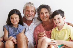 Portrait Of Grandparents With Grandchildren Sitting By Wall Stock Photo