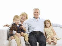 Portrait Of Grandparents And Grandchildren On Sofa Stock Photos