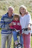 Portrait of grandparents with granddaughter sitting on bicycle Royalty Free Stock Photos