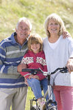 Portrait of grandparents with granddaughter sitting on bicycle Stock Photography