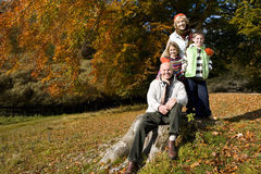 Portrait of grandparents and grandkids in field with autumn leaves Stock Images