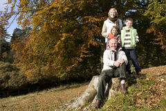 Portrait of grandparents and grandkids in grass with autumn leaves Royalty Free Stock Images