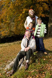 Portrait of grandparents and grandkids in grass with autumn leaves Royalty Free Stock Image
