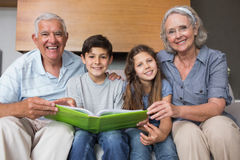 Portrait of grandparents and grandkids looking at album photo. Portrait of happy grandparents and grandkids looking at album photo in the living room stock image
