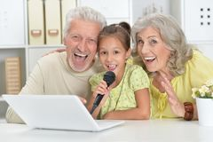 Grandparents with her granddaughter singing karaoke with tablet Stock Photography