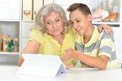 Portrait of grandson and grandmother using tablert stock photos