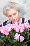 Portrait of granny behind bouquet of pink rose Stock Photos