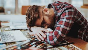 Portrait of Graphic Designer Fell Asleep at Work. Handsome Tired Sleepy Aweary Hipster Man in Glasses Lying on Hands on Table Near Laptop at Workplace. Busy stock photo