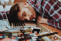 Portrait of Graphic Designer Fell Asleep at Work. Handsome Tired Sleepy Aweary Hipster Man Lying on Hands on Table Near Laptop at Workplace. Busy and Exhausted royalty free stock photo