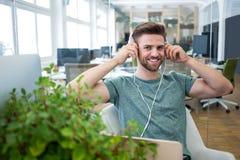 Portrait of graphic designer listening to music on head phone Stock Photo