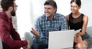 Portrait of smiling executives sitting with laptop in office. Portrait of graphic designers using laptop and digital tablet in office stock photography