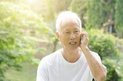 Asian old man talking on phone Royalty Free Stock Image