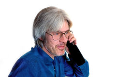 Portrait of a gray-haired, blue-eyed man with a short beard, wearing glasses. A man remembers a pleasant event and smiling on the phone Royalty Free Stock Photo
