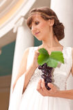 Portrait of greek woman with bunch of grapes. Portrait of beautiful greek woman with bunch of grapes in her hands against the background of a classical building royalty free stock images