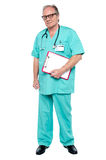 Portrait of grim faced doctor holding a clipboard Stock Photography